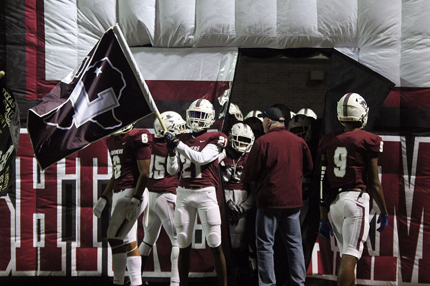 Waving the flag, senior defensive back Shadwel Nkuba II (21) prepares to run out of the tunnel after halftime.
