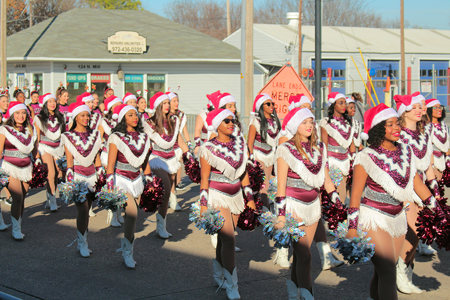 The Farmerettes walk in sync behind the band during the parade with santa hats on.