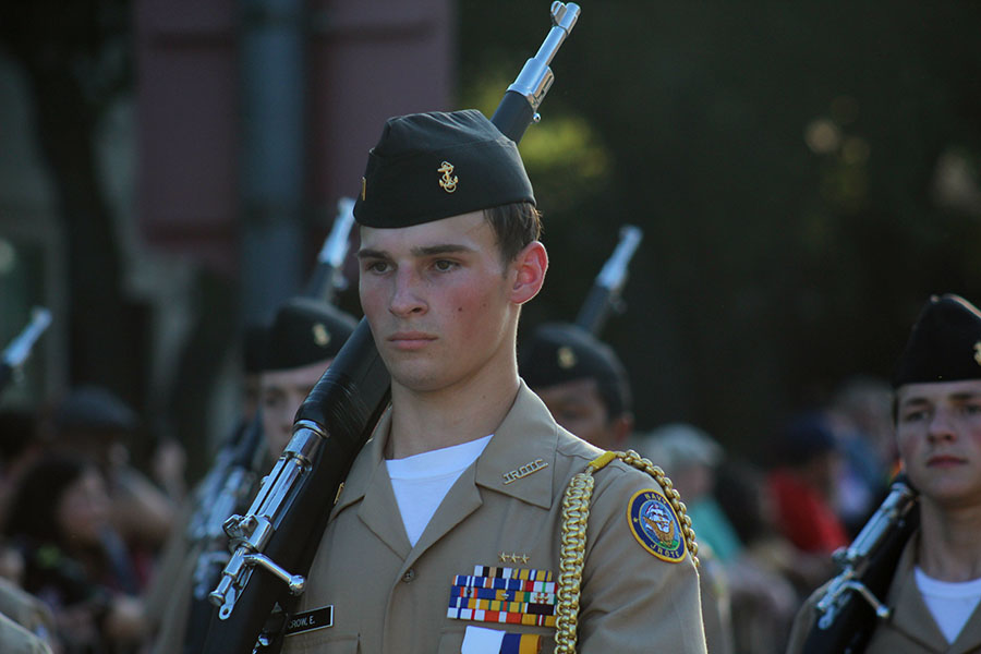 Senior Ethan Crow walks along the homecoming parade route with the NJROTC on Wednesday, Oct. 2.