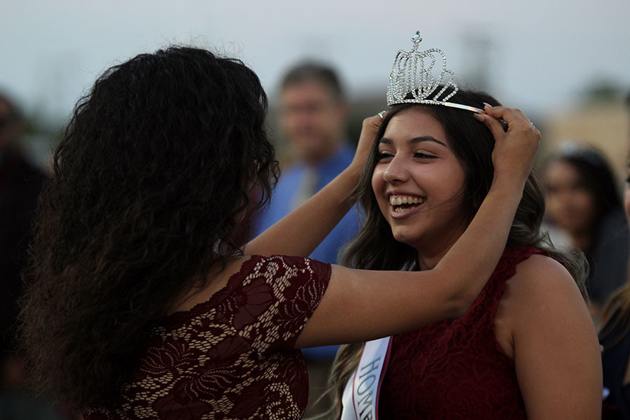 Alumna Ariana Mata crowns senior Kayla Rios as homecoming queen.