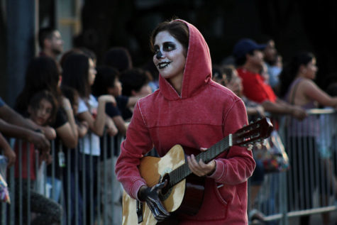 "Junior Sofia Sandoval, dressed as Miguel from ""Coco,"" plays guitar in front of the girls"