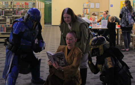 Members of Rebel Legion stand around one of cosplayers reading a book during Star Wars Reads Day on Saturday, Oct. 12.