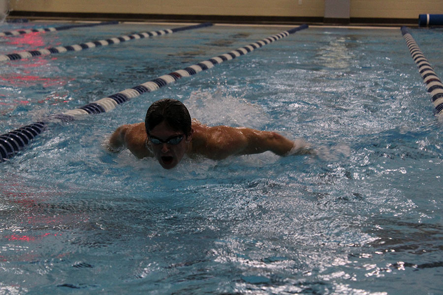 Senior Elliott Busby does a butterfly stroke during practice before school on Friday, Oct. 25.