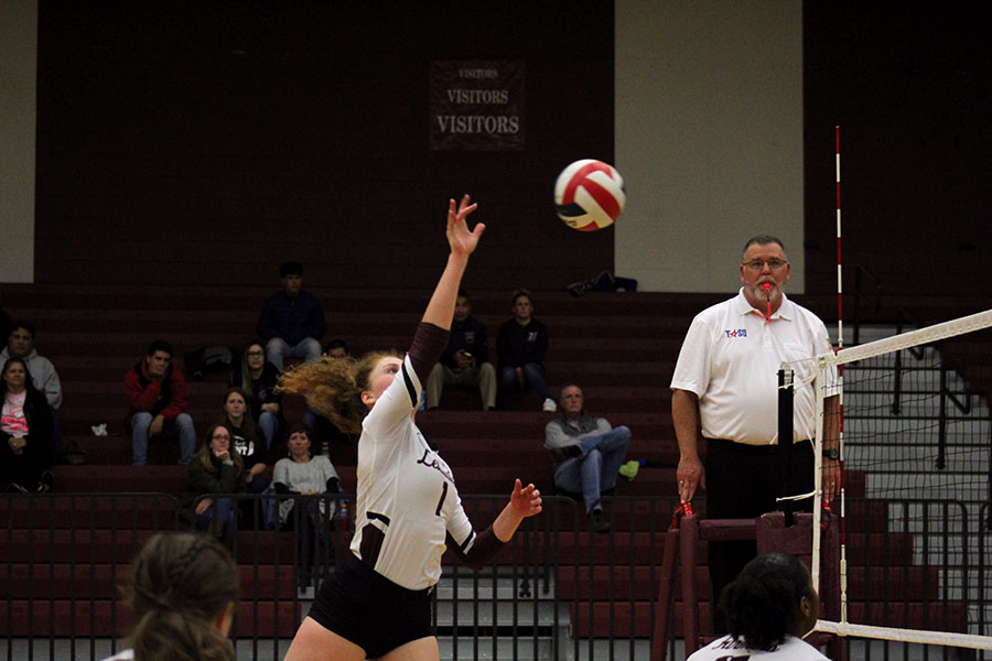 Senior Emerson Coburn spikes the ball over the net at the home game against Irving Nimitz on Friday, Oct. 25.